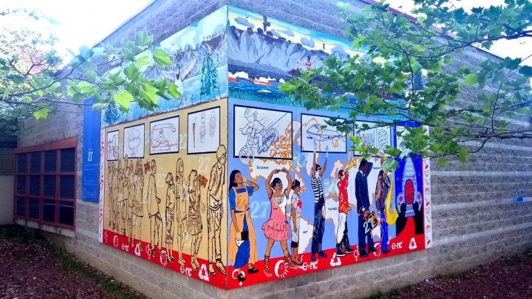 Mural of people walking and dancing on the exterior of a building
