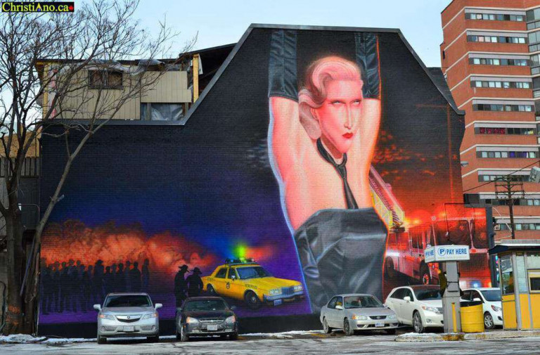 Mural on the side of a building with a person's arms upstretched wearing a tie, black dress and gloves