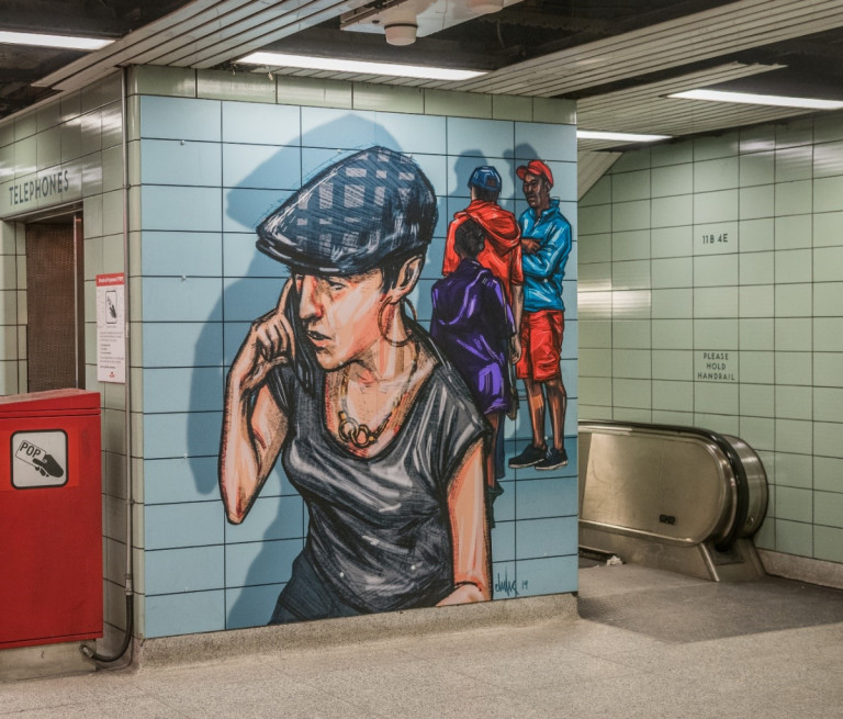 Mural of a woman on a cellphone, located in a TTC station