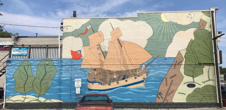 Mural of a ship in the water and cliffs