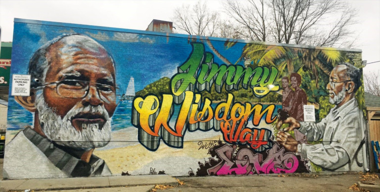Mural with large image of a man reading Jimmy Wisdom Way