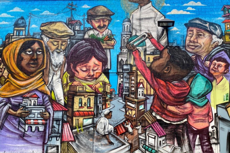 Mural of diverse people holding or surrounded by small buildings