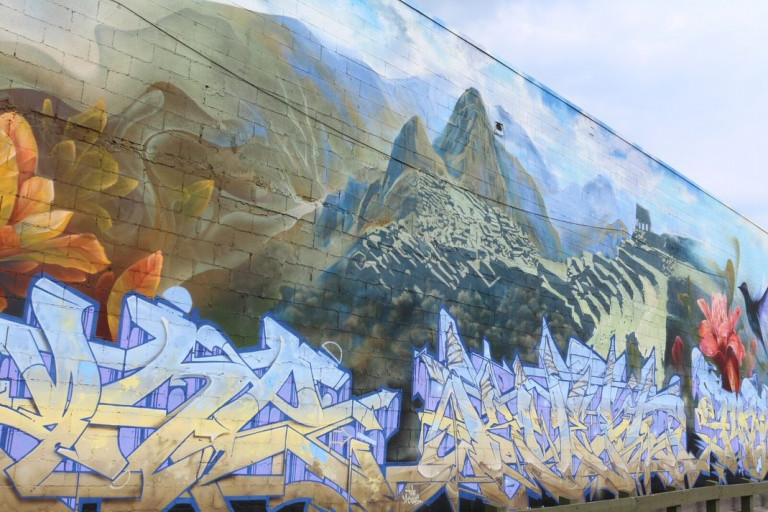 Mural with a mix of landscape and graffiti words