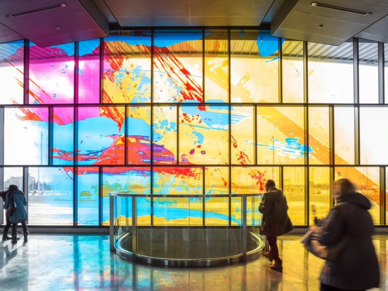 Colourful abstract mural on windows in a TTC station