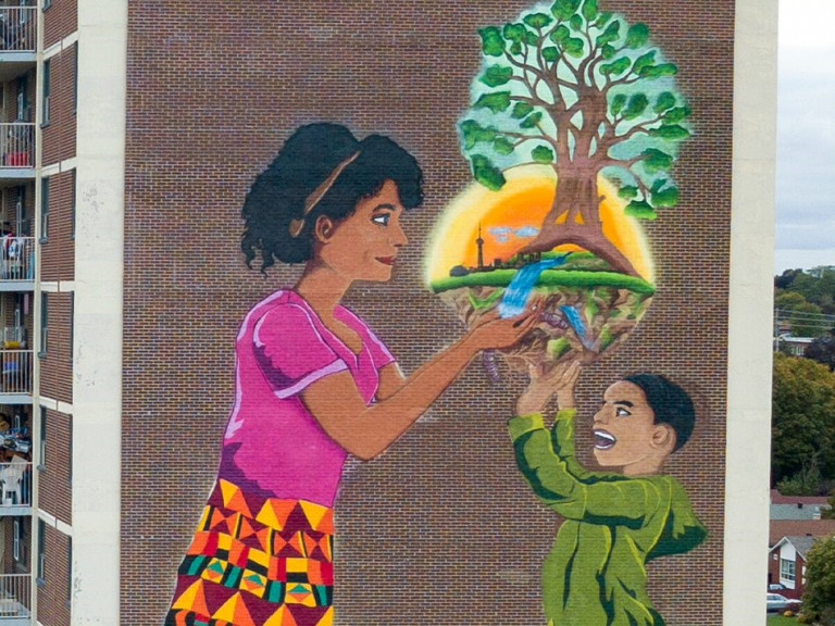 Mural of a little kid and their mother holding a tree with the silhouette of the Toronto skyline