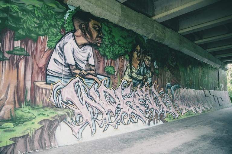 Mural under a bridge of people sitting in a forest