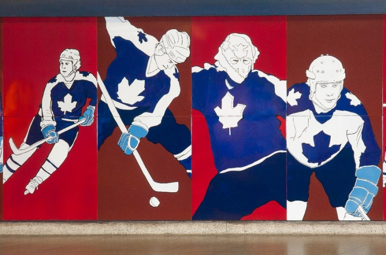 Mural of maple leaf players on a red background, located in a TTC station