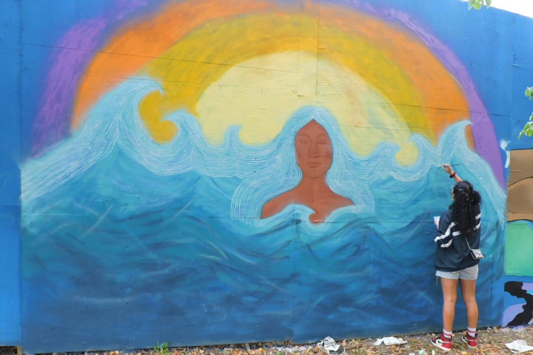 Mural of a woman surrounded by waves and the artist painting details
