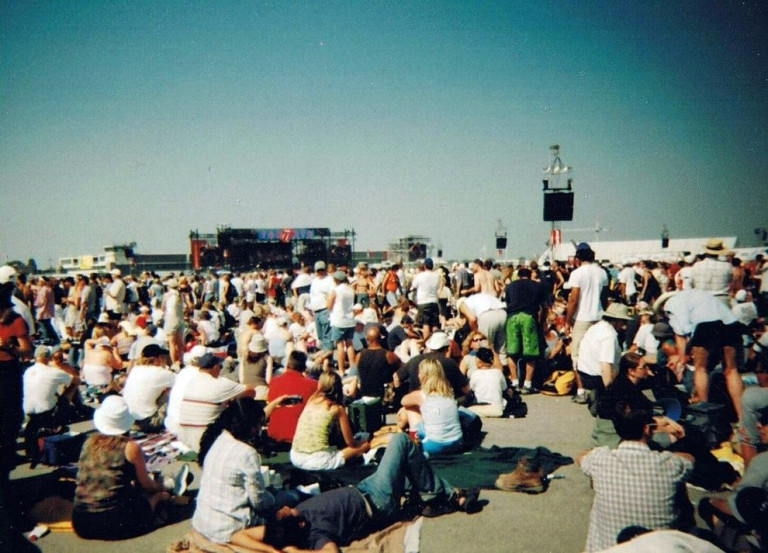 Image of a large crowd looking at a small stage in the background.