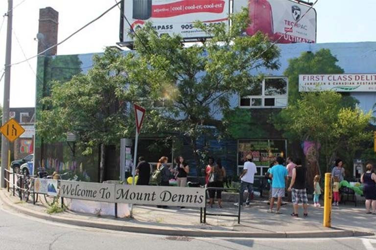 Pedestrians on a street corner with a sign reading Welcome to Mount Dennis