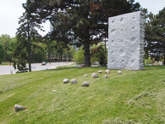 Installation of granite with scattered stones and a large stone rectangle standing upright