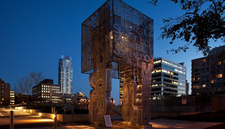 Installation in front of the night sky with tall buildings in the background