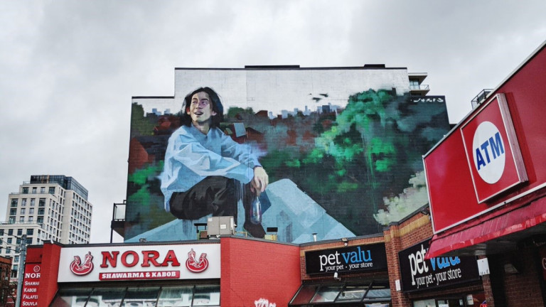 Large mural of a man above a plaza
